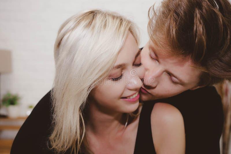Charma den härliga flickvännen få varm hjärta och lycka från grabb när hennes stiliga pojkvän som kysser och omfamnar henne i han arkivbilder