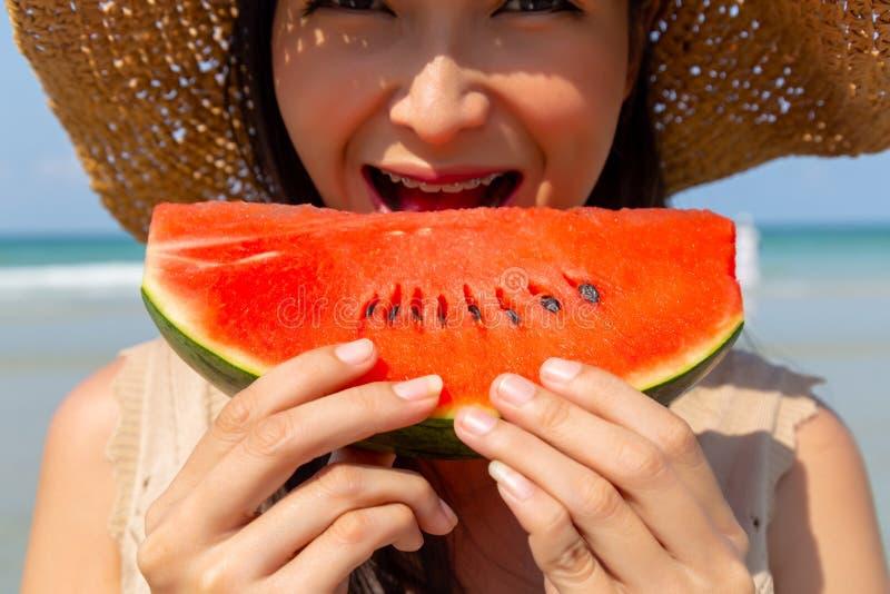 Charma den härliga unga kvinnan som äter vattenmelon för att kyla ner och släcka hennes som törstas i sommarsäsong på stranden De royaltyfri foto