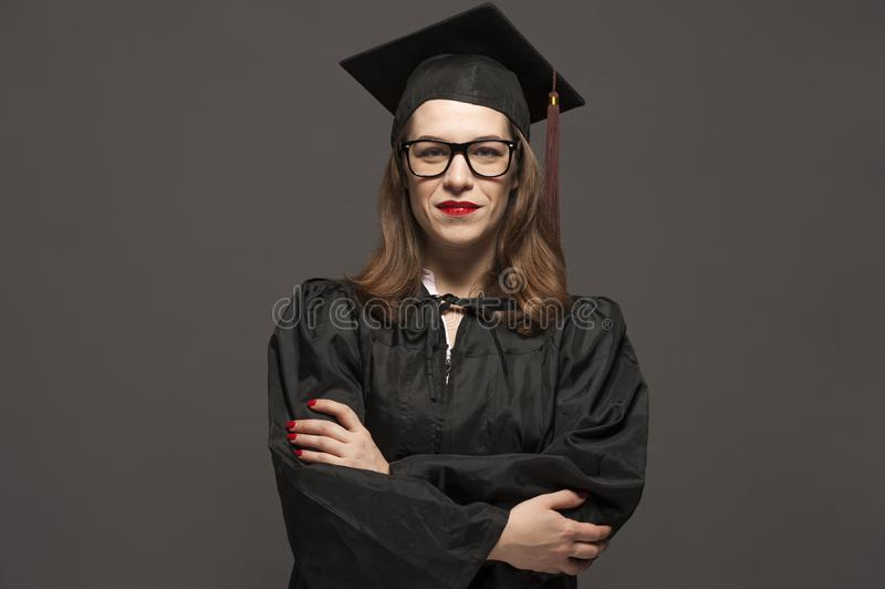 Charma den kvinnliga studenten med skäggstubbglasögon som bär det svarta ansvaret och akademikermössan royaltyfri foto