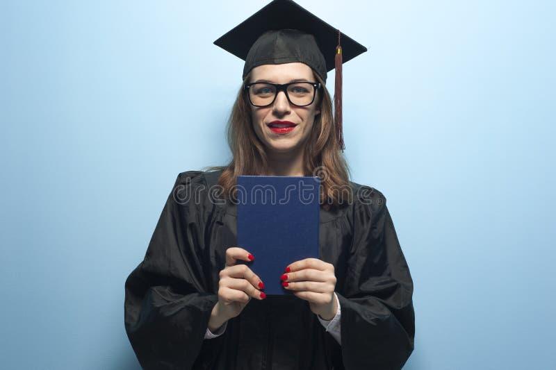 Charma den kvinnliga studenten som b?r det svarta ansvaret och st?r med diplomet i h?nder royaltyfria foton