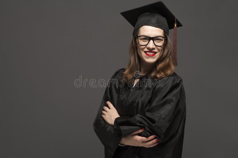 Charma den kvinnliga studenten som ler i glas?gon som b?r det svarta ansvaret arkivbild