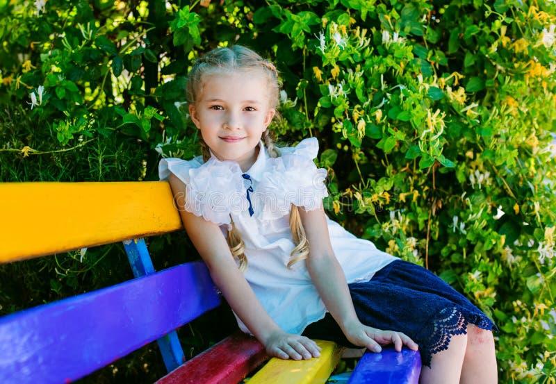 Charma den lilla skolflickan som sitter på en bänk royaltyfri foto