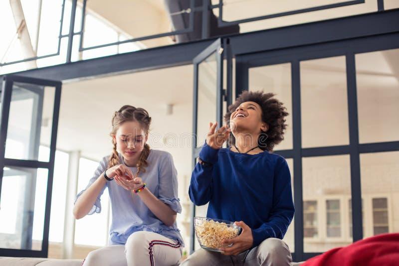 Charma den longhaired flickan som äter popcorn med nöje arkivbild