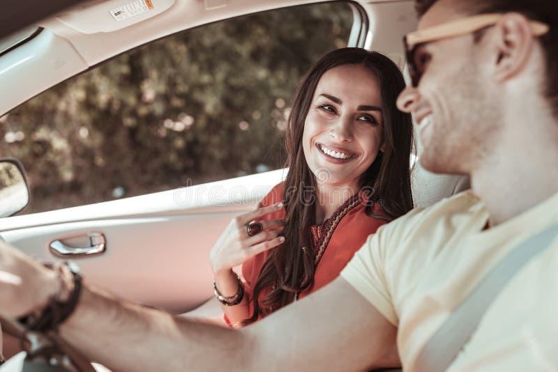 Charma den longhaired flickan som lyssnar till hennes partner arkivfoton