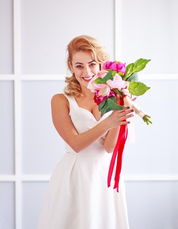 Charma den lyckliga och glade bruden f?r ung kvinna i den vita kl?nningen med buketten av blommor i studio arkivfoto