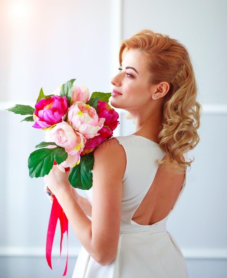 Charma den lyckliga och glade bruden f?r ung kvinna i den vita kl?nningen med buketten av blommor i studio royaltyfri bild
