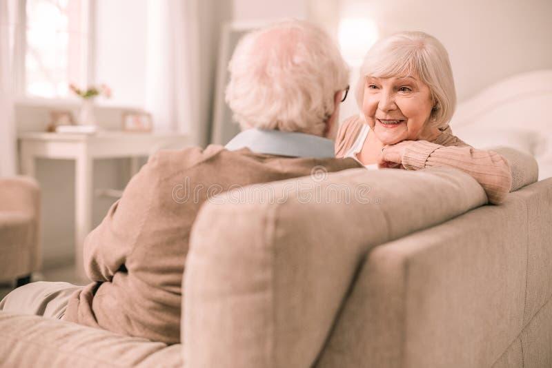 Charma den mogna kvinnan som lyssnar till hennes partner arkivbild