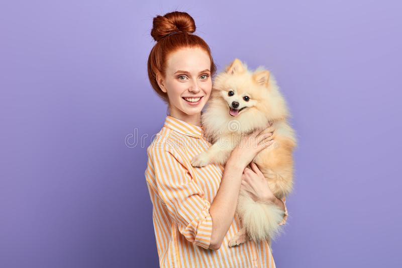 Charma den positiva flickan som omfamnar hennes fluffiga husdjur arkivbild
