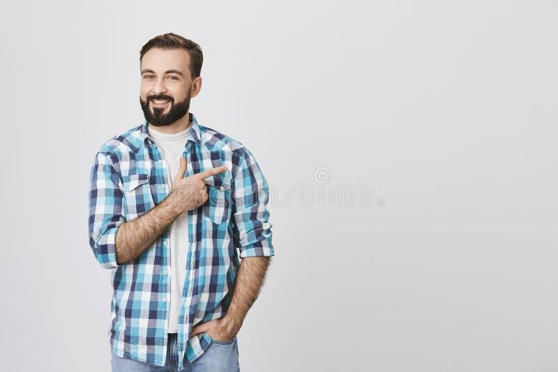 Charma den skäggiga vuxna mannen i blå plädskjorta som rätt pekar med pekfingret medan en annan hand i fack, över grå färger arkivbild