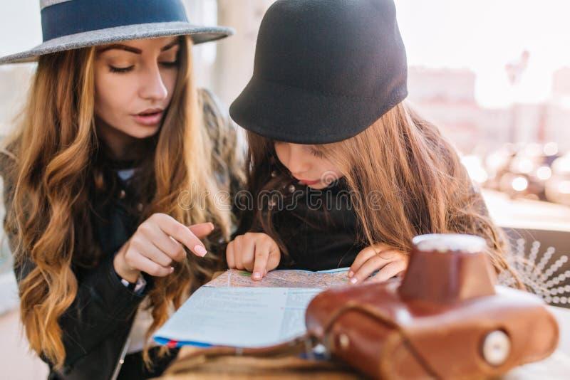 Charma den unga kvinnan i tappninghatten som ser stadsöversikten som vilar i kafé med den lilla långhåriga flickan Moderiktig gul arkivbilder