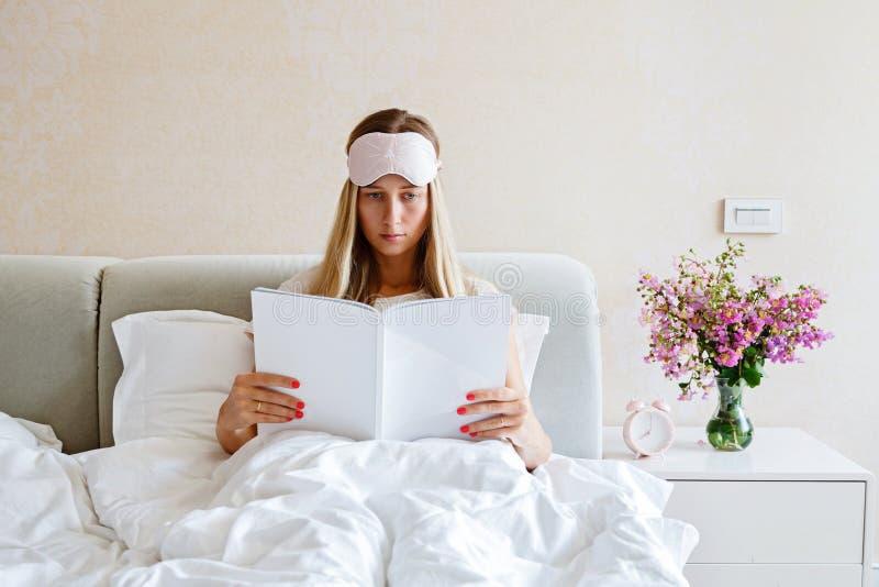 Charma den unga kvinnan med ögonbindeln på hennes tidskrift för huvudläsningmode i säng Sovrumdekor med buketten av blommor, larm arkivfoto