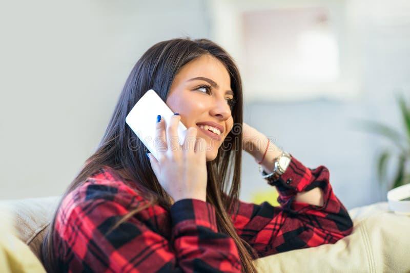 Charma den unga kvinnan som tycker om en konversation på hennes mobiltelefon, medan sitta på soffan hemma arkivbilder