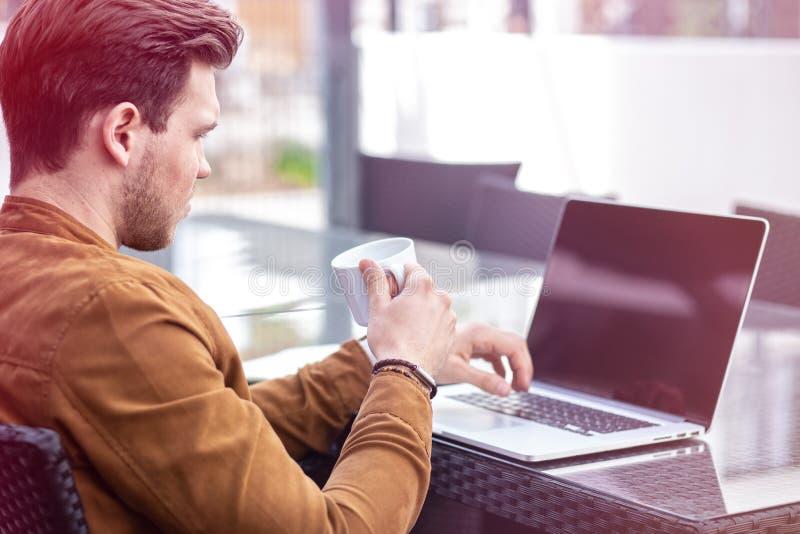 Charma den unga vuxna mannen som arbetar på bärbara datorn på den utomhus- morgonen Tid royaltyfri fotografi