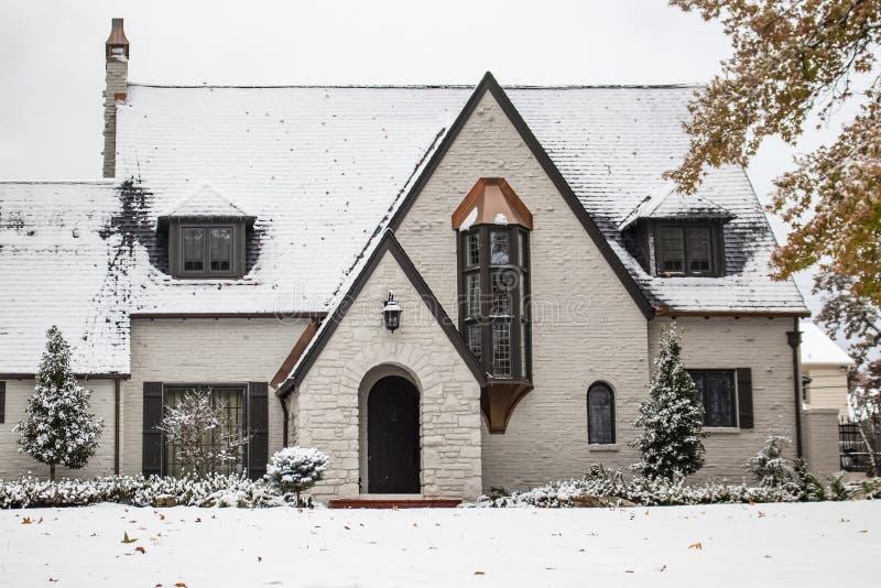 Charma den vita målade tegelstenstugan med kopparbrytningar under snöfall med höstsidor fortfarande på träd arkivfoton
