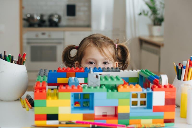 Charma förskolebarnet som spelar med dockhuskonstruktörn Liten flicka som spelar med förbindande leksakkuber royaltyfri fotografi