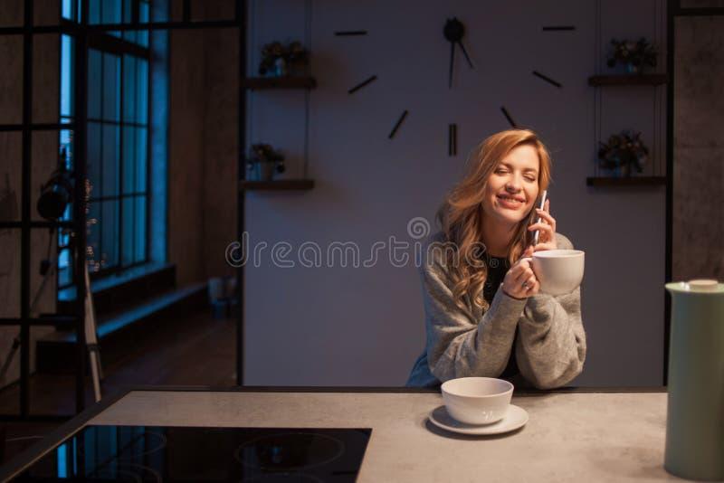 Charma flickan i köket på morgonen Samtal på telefonen och att ha frukosten en ung kvinna med rånar i hennes händer arkivbild