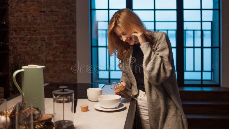 Charma flickan i köket på morgonen Samtal på telefonen och att ha frukosten en ung kvinna med rånar i hennes händer royaltyfria foton