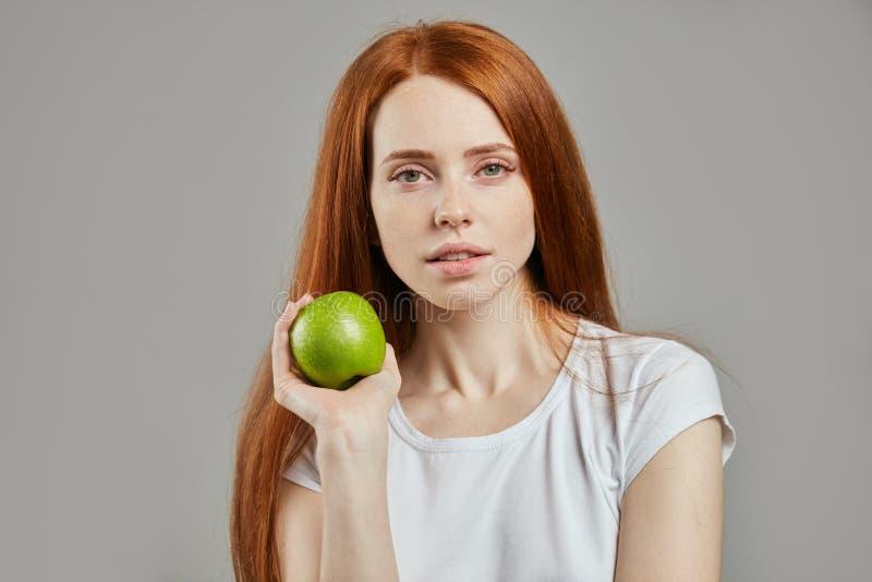 Charma flickan med det gröna äpplet som ser kameran royaltyfria bilder