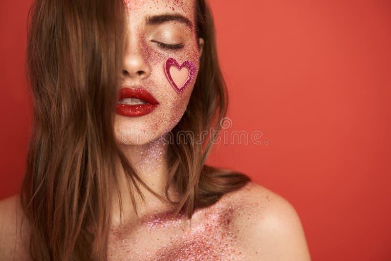 Charma flickan med glansig id?rik makeup och denformade klisterm?rken p? framsida arkivbilder