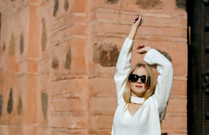 Charma flickan som bär den stack tröjan som poserar på gatan med naturligt solljus Töm utrymme fotografering för bildbyråer
