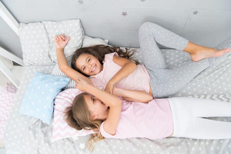 Charma gulliga ungar ha fri tid för sömn Dialogbästa vän systerskapbegrepp dela f?r hemligheter ungar arkivfoto