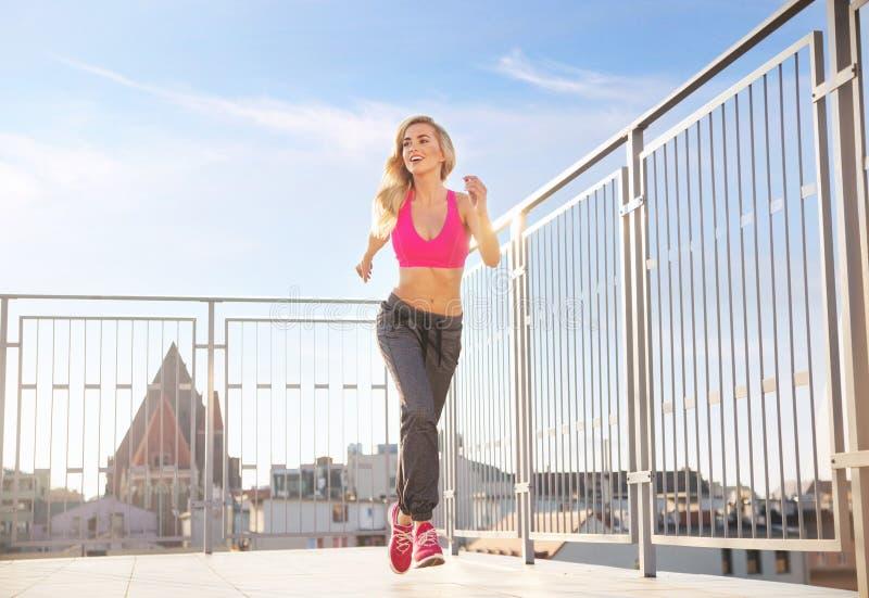 Charma idrotts- kvinnaspring på taket royaltyfria foton