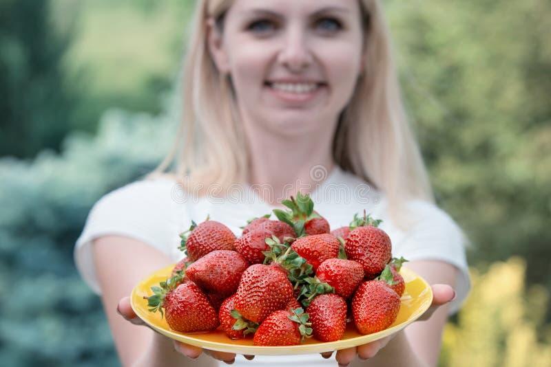 Charma kvinnan som rymmer en platta med många jordgubbar arkivfoton