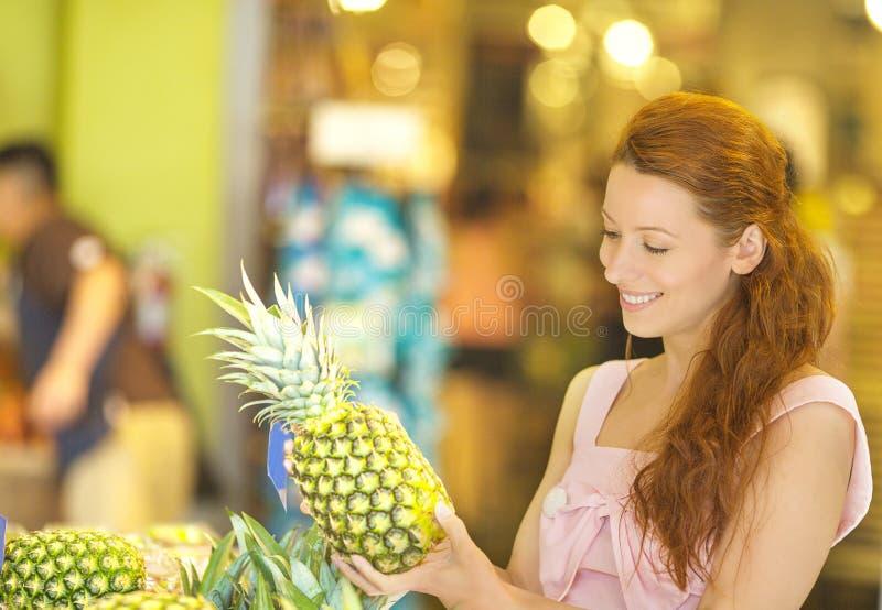 Charma kvinnan som väljer ananas, medan shoppa i livsmedelsbutik arkivfoton