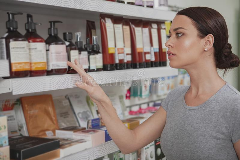 Charma kvinnashopping på apotek arkivfoto