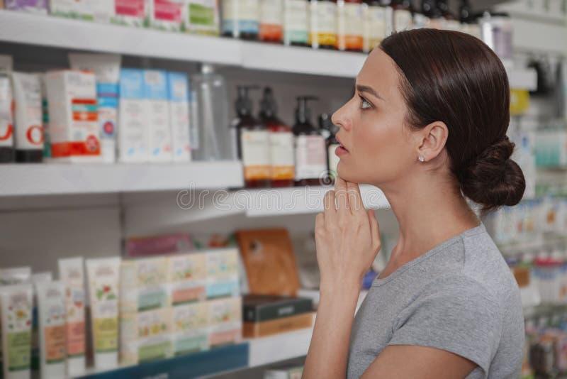 Charma kvinnashopping på apotek royaltyfria bilder