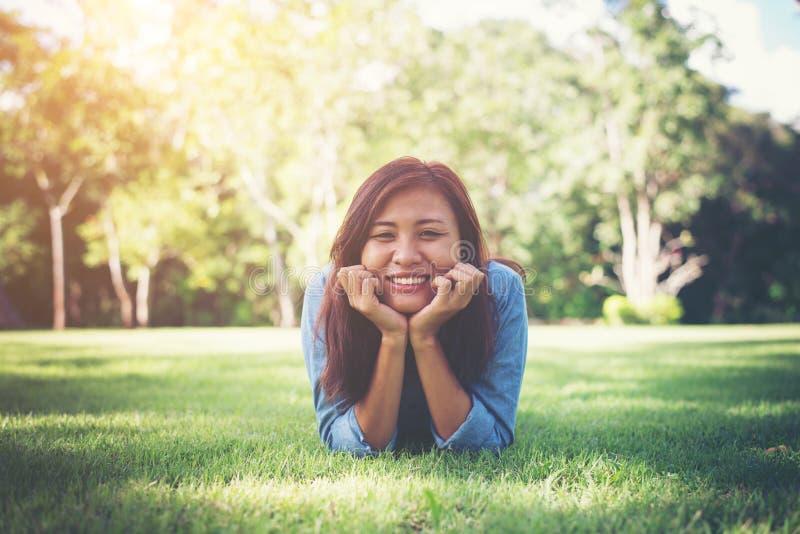 Charma le den unga hipsterkvinnan som ligger på grönt gräs arkivfoton