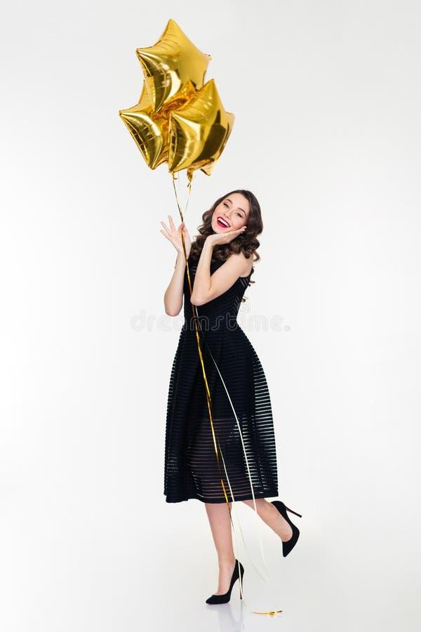Charma le unga lockiga kvinnliga innehavballonger royaltyfri bild