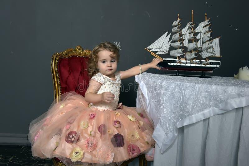 Charma lilla flickan i elegant vit med rosa sitta för klänning royaltyfri fotografi