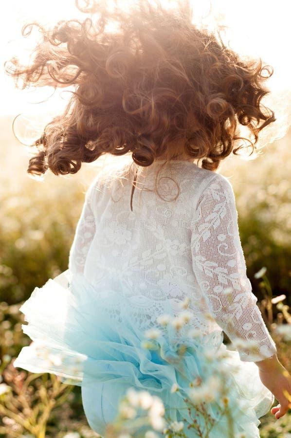 Charma lilla flickan med framkallning av lockigt hår royaltyfria bilder