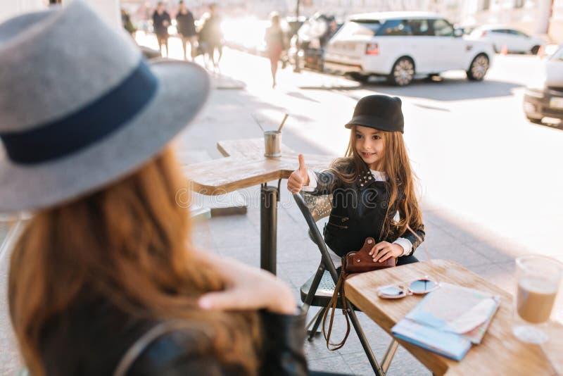 Charma lilla flickan med mörka ögon som sitter på trätabellen som rymmer tappningkameran och visar upp tummen stilfullt arkivbilder