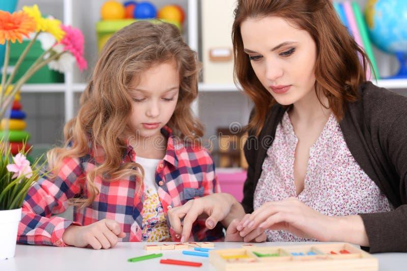 Charma lilla flickan med mamman för att lära att räkna med pinnar royaltyfri bild