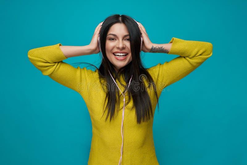 Charma lyssnande musik för modell med hörlurar som ler royaltyfri foto