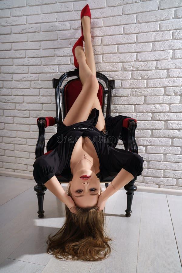 Charma modellen i den svarta klänningen som poserar på stol i studio royaltyfri fotografi