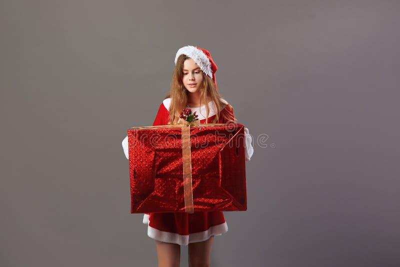 Charma mrsen Iklädda Claus den röda ämbetsdräkten, jultomten hatt och vita handskehåll i hennes händer den enorma julklappen arkivbilder