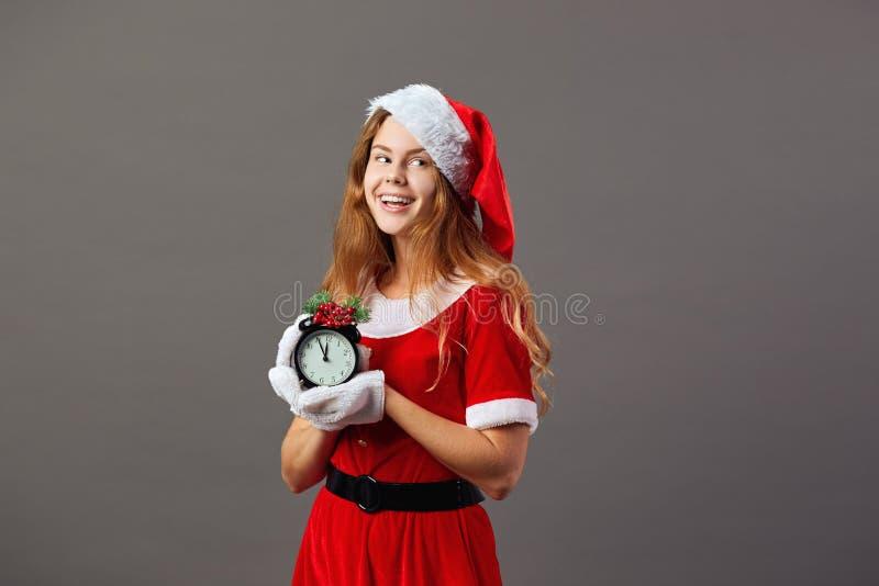 Charma mrsen Iklädda Santa Claus den röda ämbetsdräkten, jultomten hatt och vita handskar rymmer en klocka som visar fem till arkivfoton