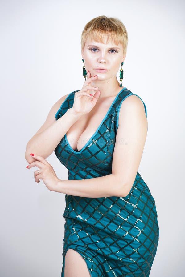 Charma som är ungt plus formatkvinna med iklätt kort blont hår en lyxig lång aftongräsplanklänning med paljetter och ställningar  arkivfoton
