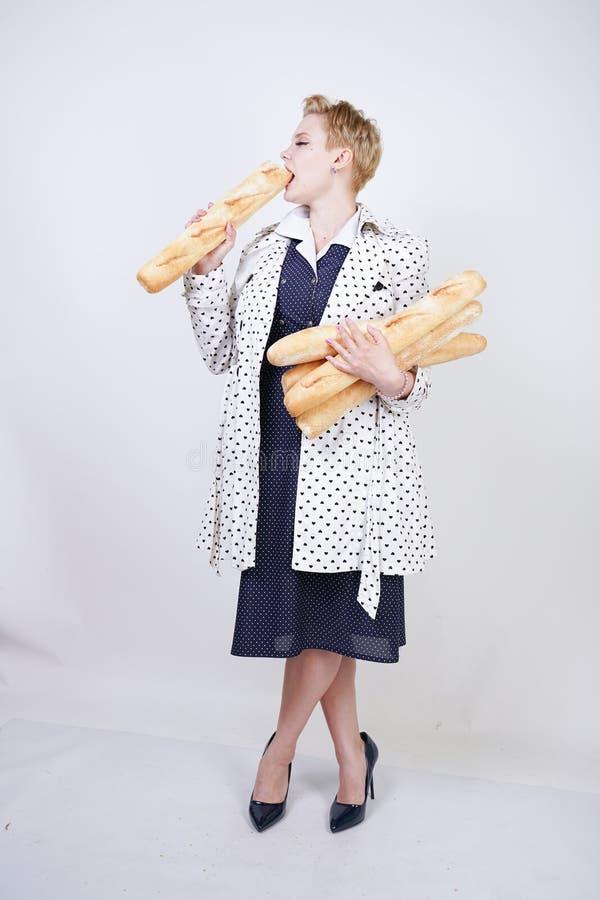 Charma utvikningsbrudkvinnan med kort hår i ett vårlag med prickar som poserar med bagetter och att tycka om dem på en vit backgr arkivfoton