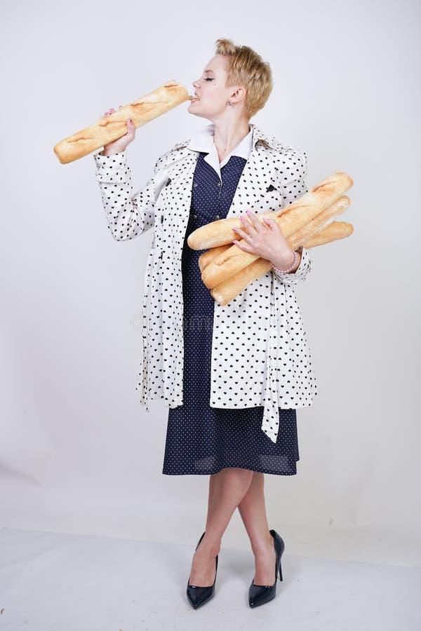 Charma utvikningsbrudkvinnan med kort hår i ett vårlag med prickar som poserar med bagetter och att tycka om dem på en vit backgr fotografering för bildbyråer