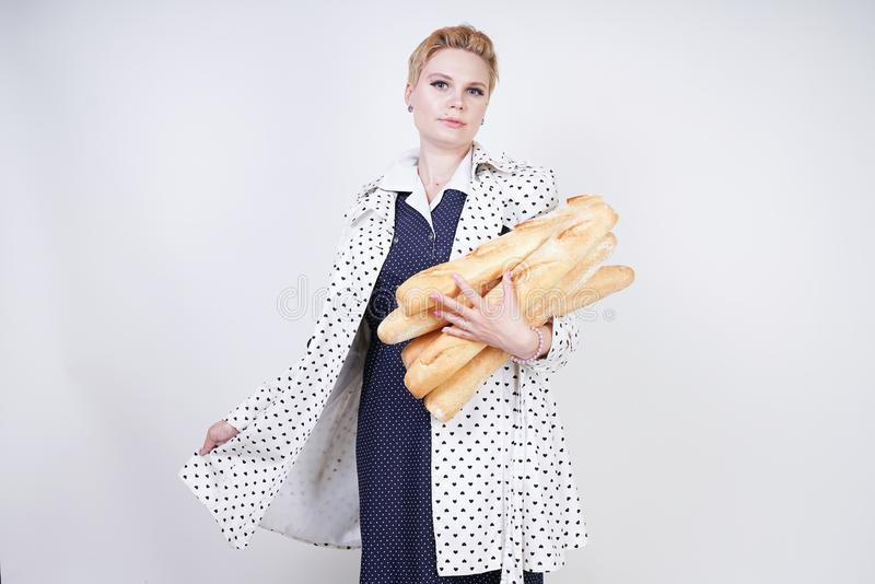 Charma utvikningsbrudkvinnan med kort hår i ett vårlag med prickar som poserar med bagetter och att tycka om dem på en vit backgr royaltyfri fotografi