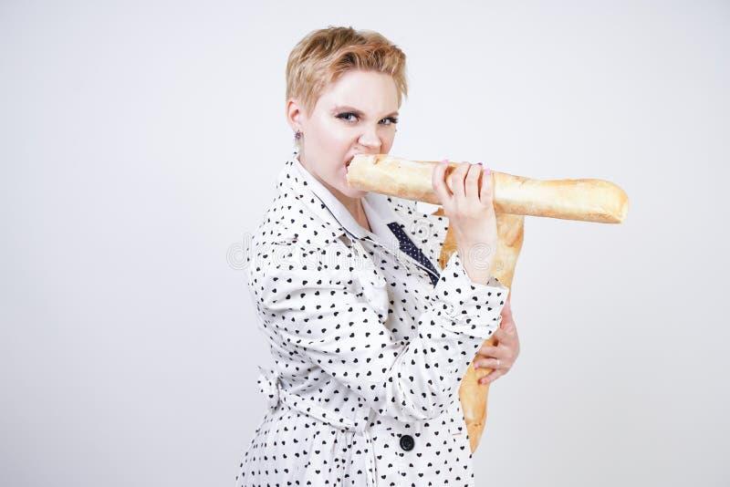 Charma utvikningsbrudkvinnan med kort hår i ett vårlag med prickar som poserar med bagetter och att tycka om dem på en vit backgr arkivbild