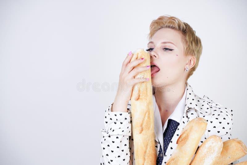 Charma utvikningsbrudkvinnan med kort hår i ett vårlag med prickar som poserar med bagetter och att tycka om dem på en vit backgr arkivfoto