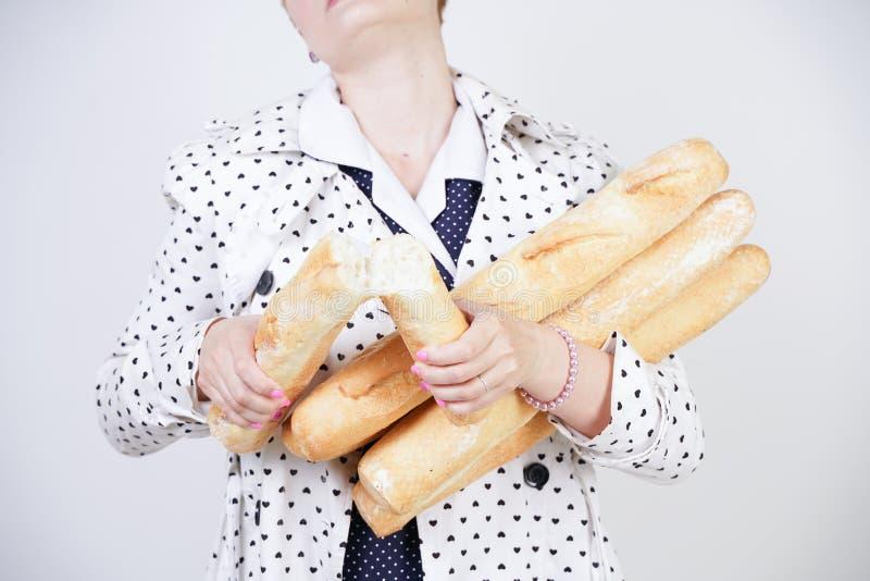Charma utvikningsbrudkvinnan med kort hår i ett vårlag med prickar som poserar med bagetter och att tycka om dem på en vit backgr royaltyfria foton