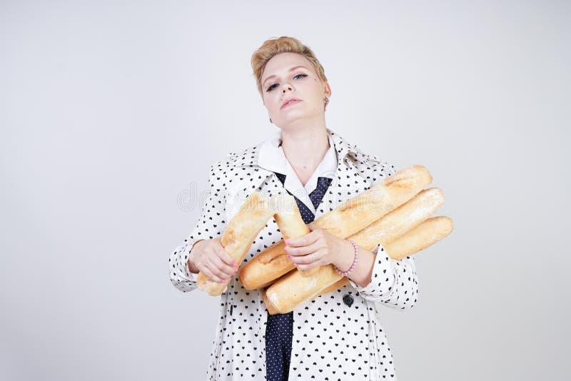 Charma utvikningsbrudkvinnan med kort hår i ett vårlag med prickar som poserar med bagetter och att tycka om dem på en vit backgr royaltyfri foto