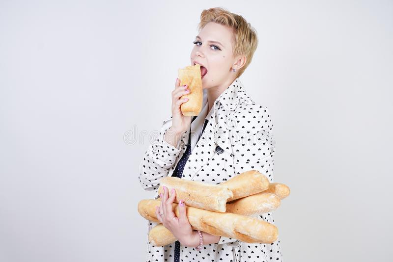 Charma utvikningsbrudkvinnan med kort hår i ett vårlag med prickar som poserar med bagetter och att tycka om dem på en vit backgr royaltyfri bild