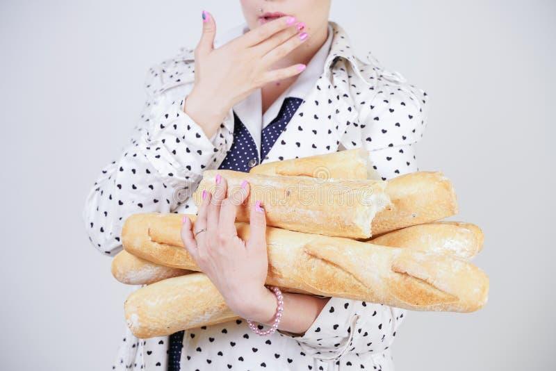 Charma utvikningsbrudkvinnan med kort hår i ett vårlag med prickar som poserar med bagetter och att tycka om dem på en vit backgr arkivbilder